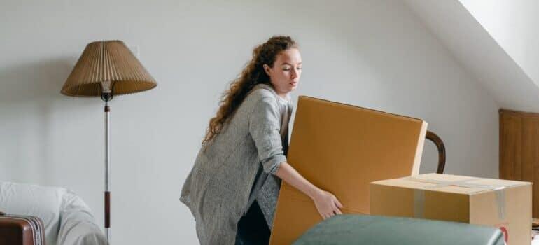 zena koja nosi kartonsku kutiju
