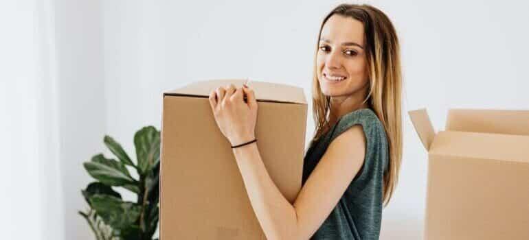 Devojka sa kutijom u ruci, u sred selidbe