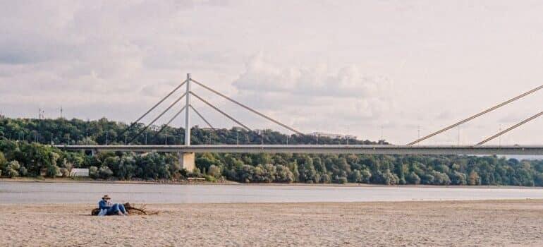 reka, čovek na plaži i most u daljini