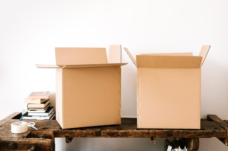 kartonske kutije i knjige na stolu čekaju na međunarodni kombi prevoz