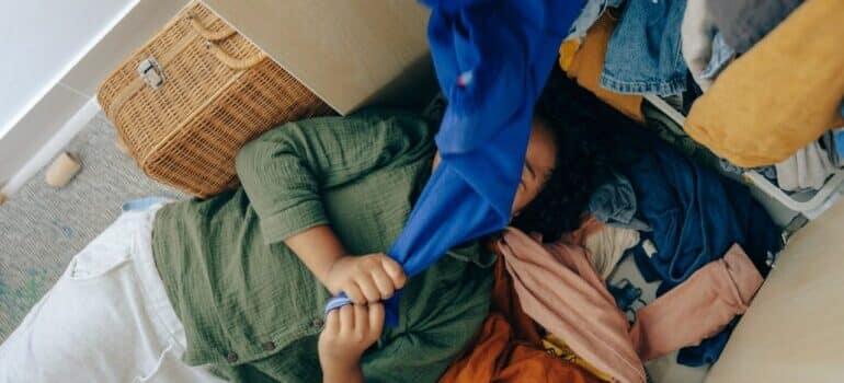 osoba koja leži uspred ormana punog stvari i drži jednu od njih planira d aiznajmi skladište beograd