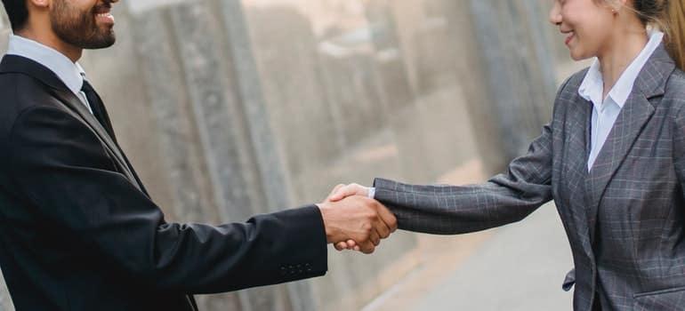 Muškarac i žena se zadovoljno rukuju