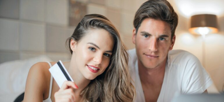 momak i devojka sa laptopom na krevetu i platnom karticom razmišljaju koja je selidbe cena