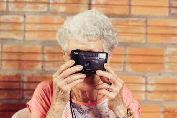 Starija žena sa fotoaparatom dobro raspoložena što govori da nije teškoda pomognete starijima da se presele u Beograd