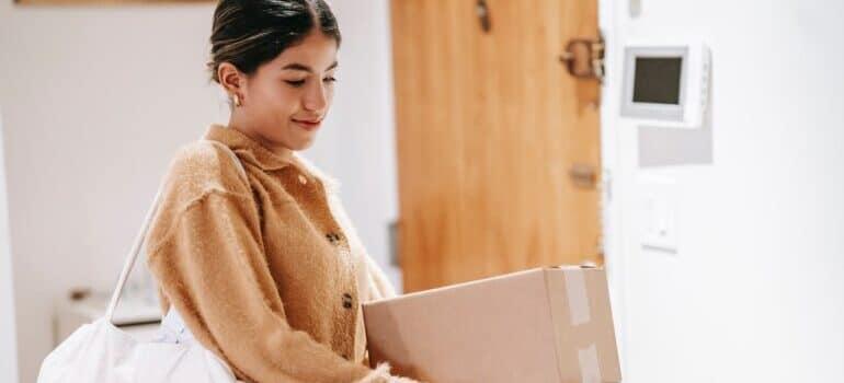 Devojka nosi kutije u toku selidbe Bor