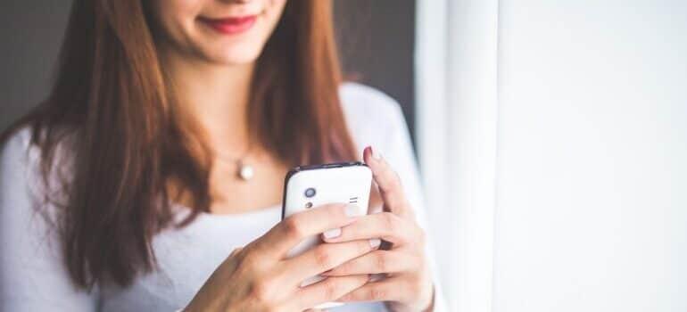 Nasmejana žena drži telefon
