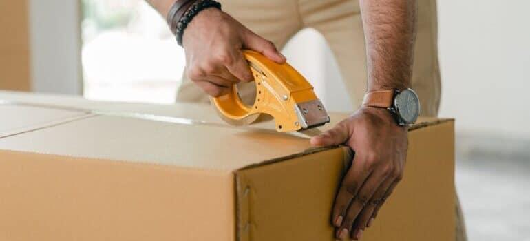 Čovek pakuje kutije za selidbe Novi Pazar