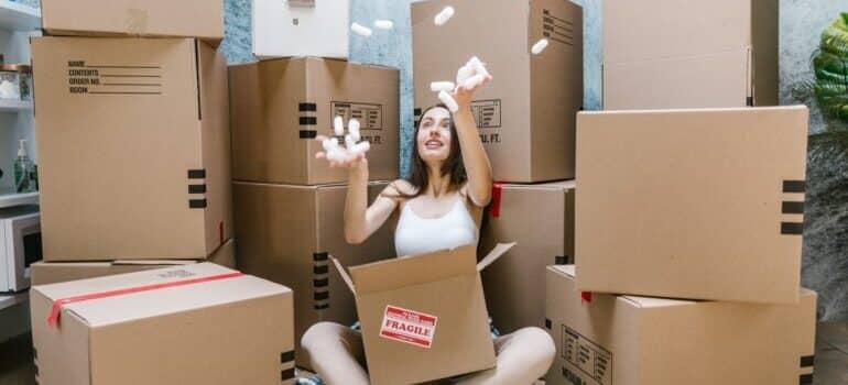 Nasmejana žena sedi među kutijama za selidbu