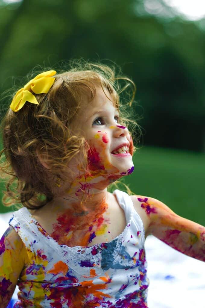 Devojčica sa bojama koja pokazuje da se sa decom treba i igrati kada se spremate da se preselite u Nemačku sa decom