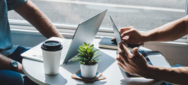 Ljudi sede za stolom i kucaju na laptopovima