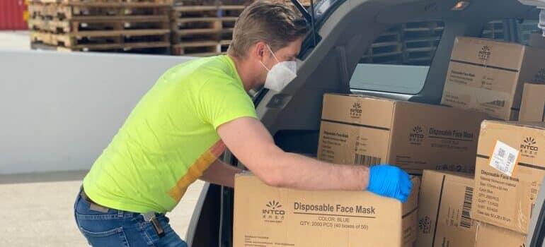 Čovek pakuje kutije u gepek