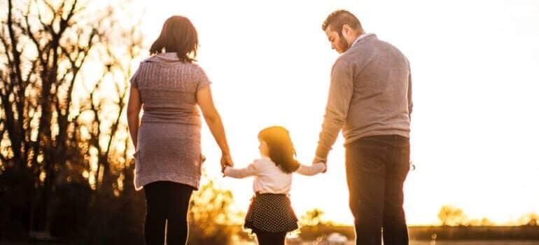 Porodica se drzi za ruke i gleda zalazak sunca