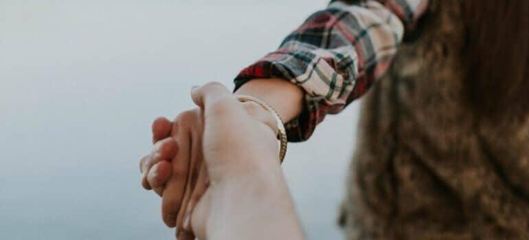 Dvoje se drže za ruke