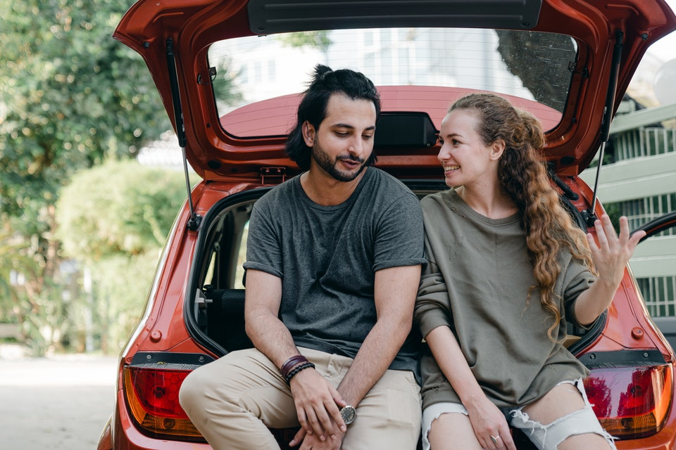 Dečko i devojka u procesu selidbe sede na automobilu i razgovaraju