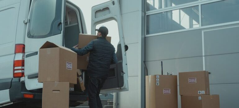 Radnik utovara kutije u kombi.